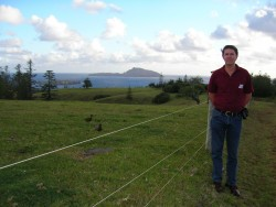 Max standing beside his ancestor's land on Norfolk Island